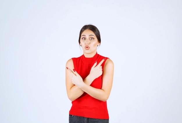 Ragazza in camicia rossa che punta su entrambi i lati.