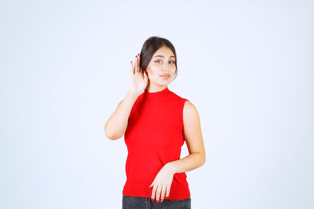 Girl in red shirt pointing her ear to hear well.