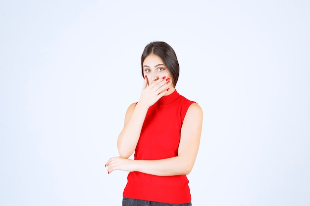 Girl in red shirt pointing at her mouth and asking for silence.