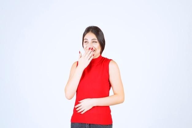Ragazza in camicia rossa che indica la sua bocca e chiede silenzio.