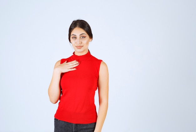 Girl in red shirt pointing at herself .