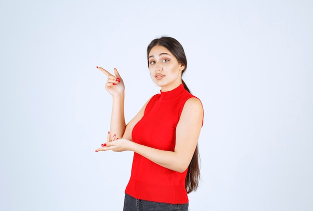 Girl in a red shirt pointing to the left side.