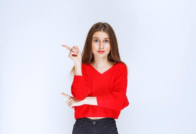 Ragazza in camicia rossa che indica il lato sinistro.