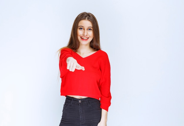Girl in red shirt pointing at the person ahead.