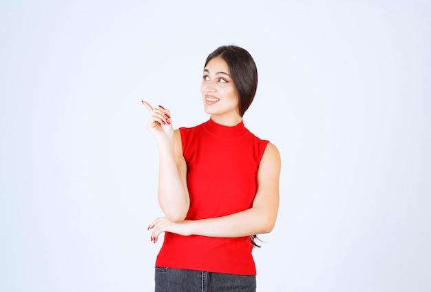 Ragazza in camicia rossa che indica qualcosa a sinistra.