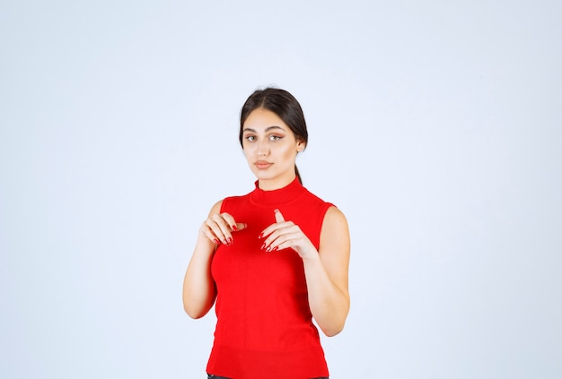 Girl in red shirt pointing somewhere below.