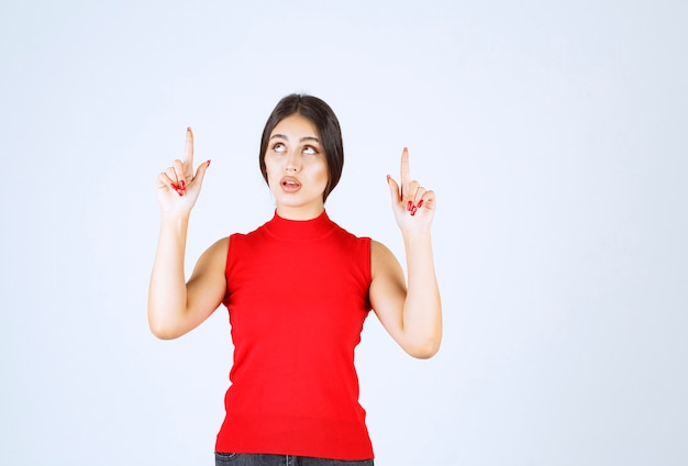 Girl in red shirt pointing upside.