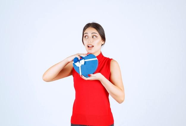 Ragazza in camicia rossa che presenta la sua confezione regalo a forma di cuore blu.