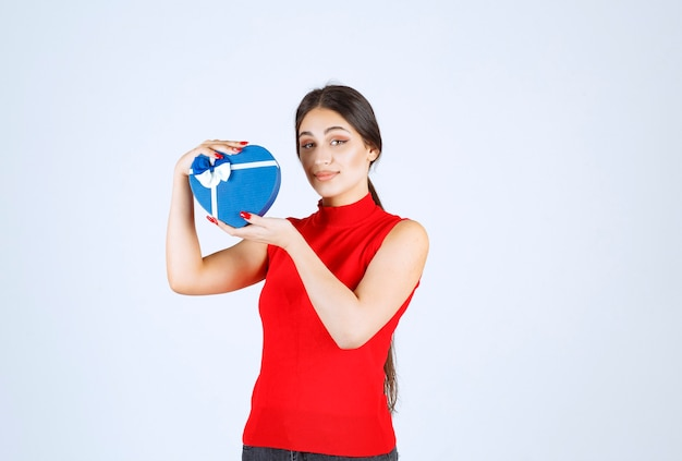 Girl in red shirt presenting her blue heart shape gift box.