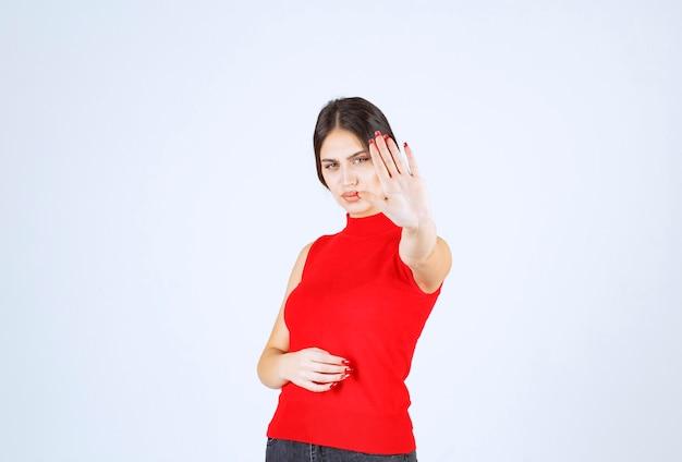 Ragazza in camicia rossa che si impedisce qualcosa.
