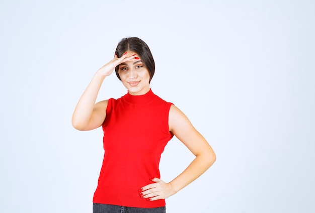 Girl in red shirt putting hand to her forehead and looking forward.