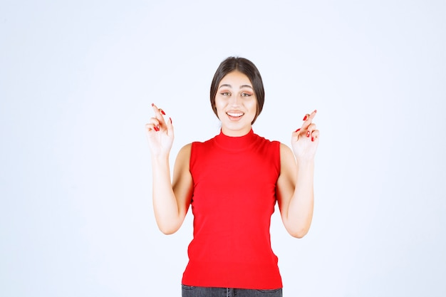 Girl in red shirt showing finger cross sign.