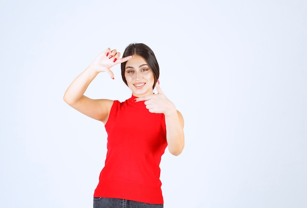 Girl in red shirt showing photo capturing hand sign.