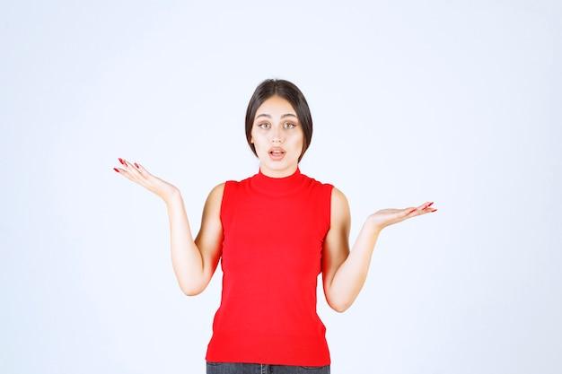 Ragazza in camicia rossa che mostra qualcosa nella sua mano aperta.