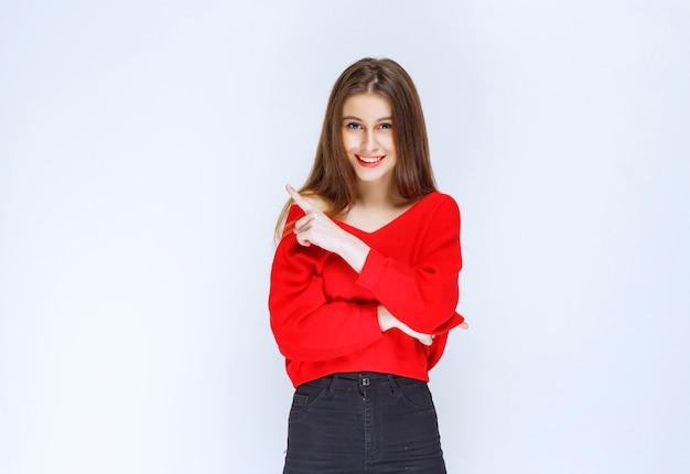 Ragazza in camicia rossa che mostra qualcosa sul lato sinistro.
