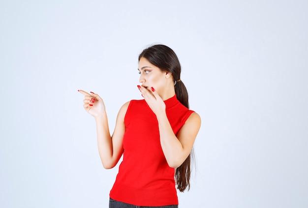 Ragazza in camicia rossa che mostra qualcosa a sinistra.