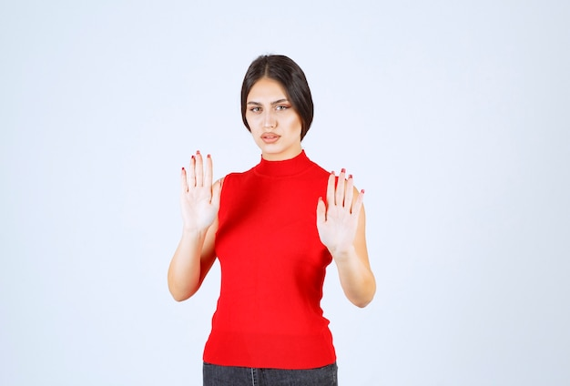 Girl in a red shirt stopping something with hands.