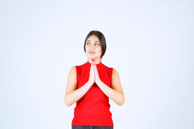 Girl in red shirt uniting hands and praying.