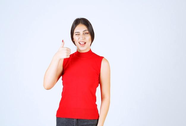 La ragazza in camicia rossa strizza l'occhio e mostra la sua soddisfazione.