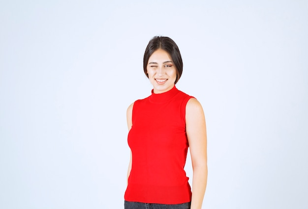 Girl in red shirt winkles and shows her satisfaction.