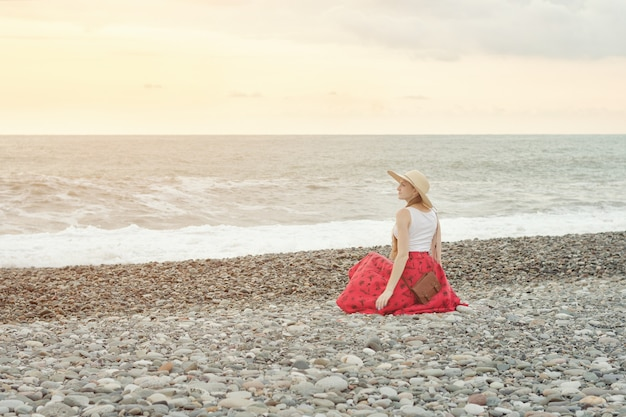 Girl in red skirt and hat sits on the seashore. sunset time. back view