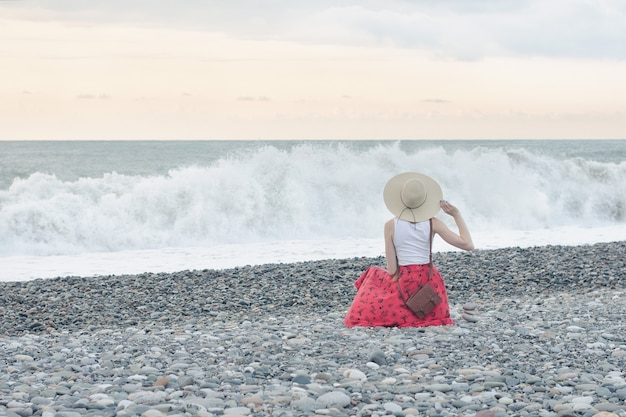 Girl in red skirt and hat sits on the seashore.