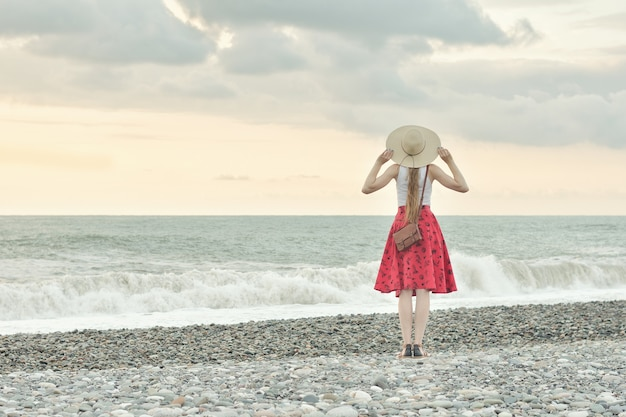 Girl in red skirt and hat standing by the sea