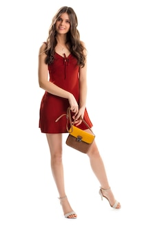 Girl in red sleeveless dress. keyhole dress and bag. evening outfit with accessories. model wears beautiful summer clothes.