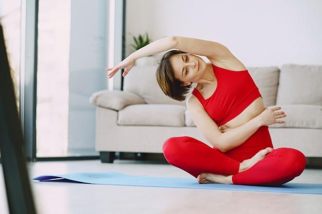 Ragazza in uniforme sportiva rossa praticando yoga a casa