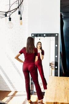 女の子の赤いスーツスタンドミラー、大きな鏡、反射、スーツを試着、仕立て、服装、パーティーまたはパーティーに行く