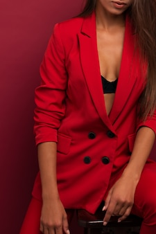 Girl in a red suit with a beautiful press on the stomach. studio burgundy background.