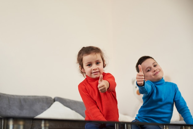 A girl in red sweater sitting on the sofa near a boy in blue sweater showing thumbs up and smiling at the camera