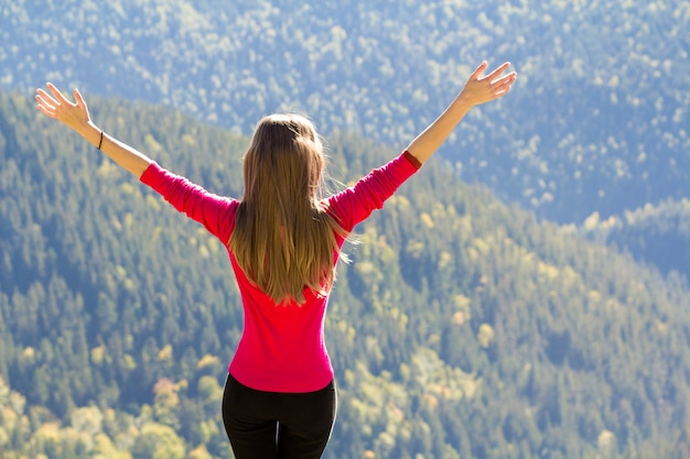 Girl in red sweater standing on big rocks in mountains lifting hands