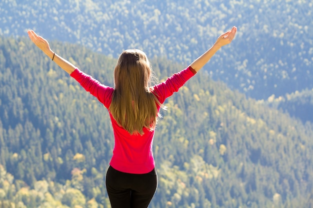 Girl in red sweater standing on big rocks in mountains lifting hands.