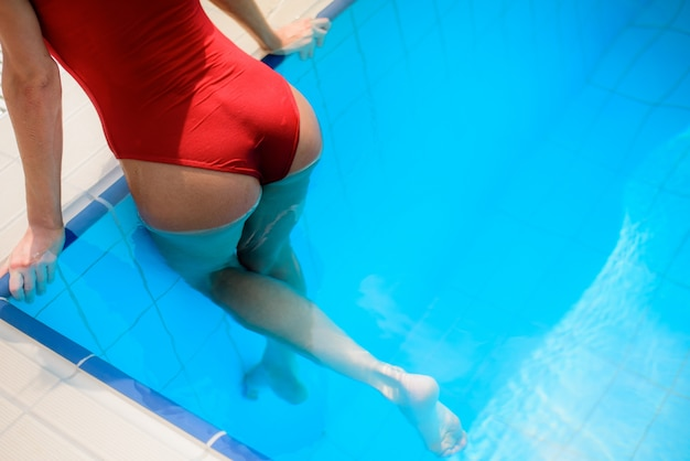Girl in red swimsuit in blue swimming pool