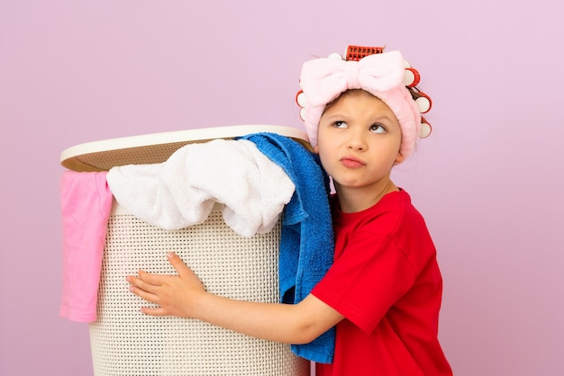A girl in a red t-shirt holds a basket of dirty laundry.