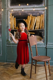 Girl in a red velvet dress holding a red rose on the background of the bakery