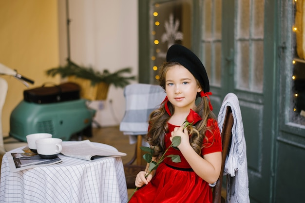A girl in a red velvet dress sits at a cafe table and holds a red rose in her hands