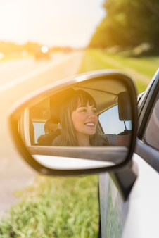 Girl reflected on side mirror