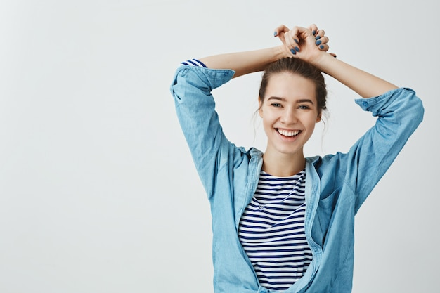 Girl relaxes after spending day in college. studio shot of good-looking emotive student holding hands on hair while smiling broadly and being carefree, expressing positive emotions over gray wall