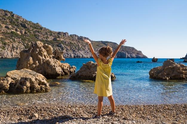 Девушка ослабляя против предпосылки голубого неба и моря.