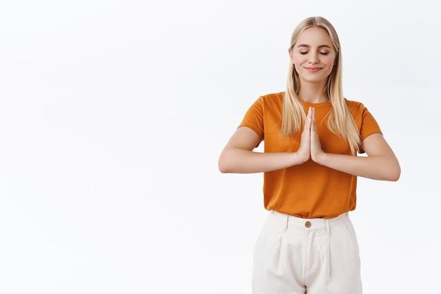 Ragazza che si rilassa durante lo yoga mattutino. attraente donna bionda in maglietta arancione premere i palmi insieme sul petto per meditare, sorridere soddisfatto chiudere gli occhi, eseguire esercizi di respirazione, sfondo bianco