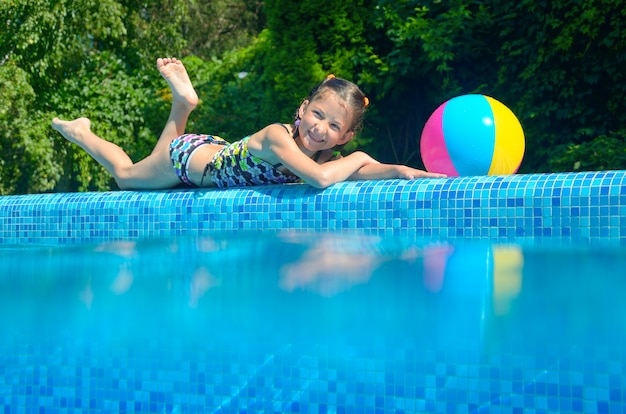 Girl relaxing near pool, underwater and above view, kid on summer vacation