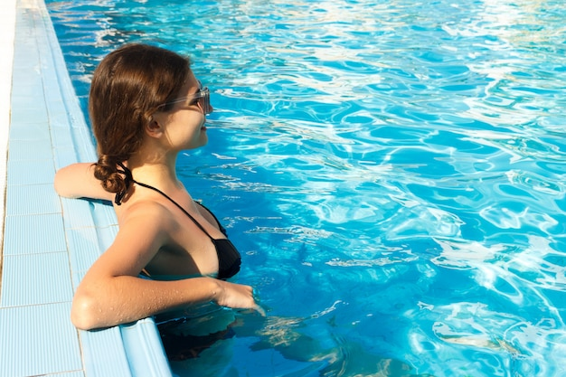 Girl relaxing near swimming pool. summer vacations