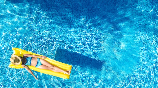 Girl relaxing in swimming pool, child swims on inflatable mattress and has fun in water, tropical holiday resort, aerial drone view from above