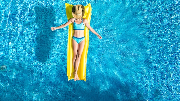 Girl relaxing in swimming pool on inflatable mattress
