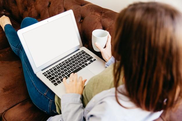 Ragazza rilassante con drink e laptop
