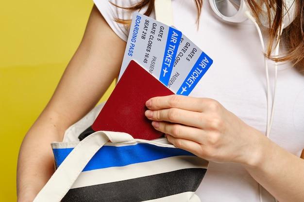 Девушка снимает билеты с паспортом в сумке.