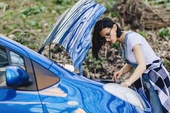 女の子は道路上の開いたフードが付いている車を修理します