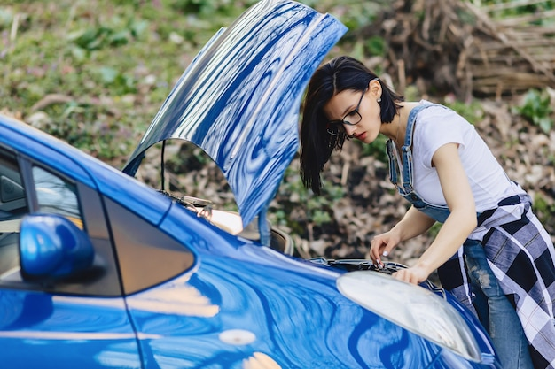Girl repairs car with an open hood on road